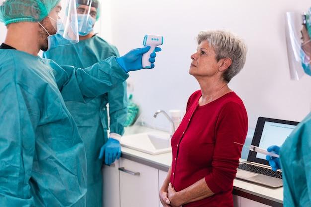 Medisch personeel dat koorts meet bij een oudere vrouw tijdens een pandemie van het coronavirus - arts en verpleegkundige screenen mensen op de ziekte van covid 19