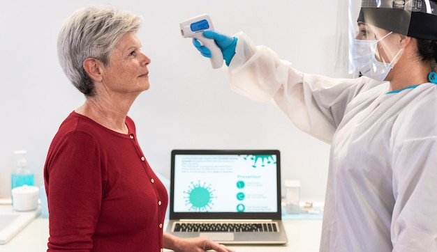 Medisch personeel dat koorts meet bij een vrouw tijdens een pandemie van het coronavirus - arts en verpleegkundige screenen mensen op de ziekte van covid 19