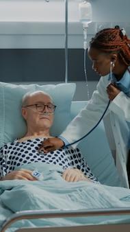 Medisch personeel dat zieke patiënt in ziekenhuisafdeling raadpleegt