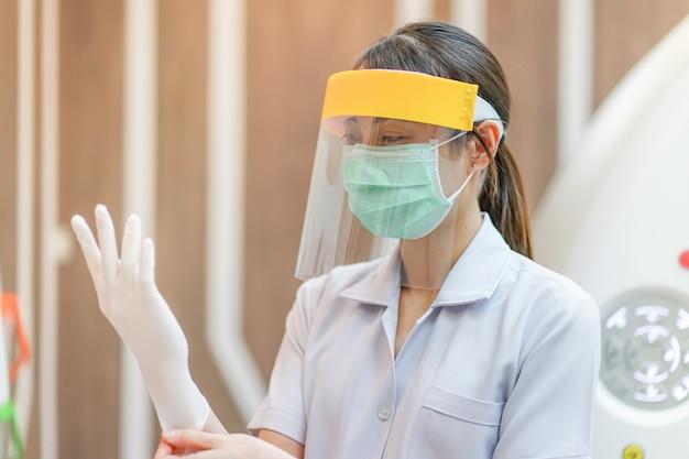 Medisch personeel draagt een gelaatsscherm, een medisch masker en een medisch bosje ter bescherming van het coronavirus covid-19 virus in het ziekenhuis