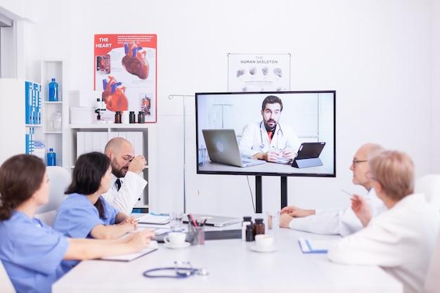Medisch personeel in gesprek met deskundige arts tijdens webinar in de vergaderruimte van het ziekenhuis. medicijnpersoneel dat internet gebruikt tijdens online ontmoeting met deskundige arts voor expertise.