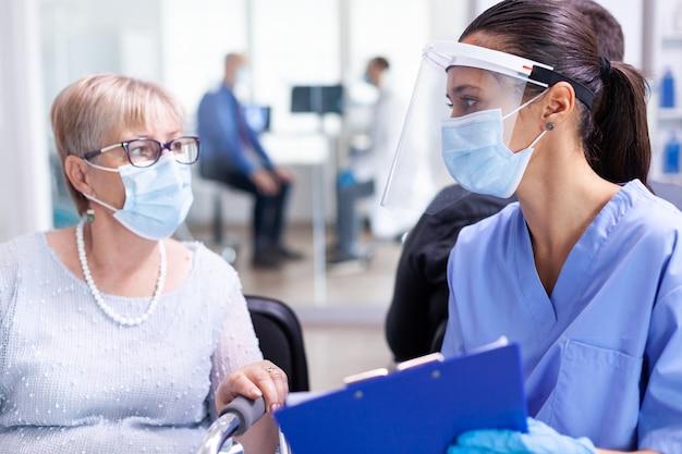 Medisch personeel met gehandicapte oudere vrouw in gesprek over herstelbehandeling in de wachtruimte van het ziekenhuis met gezichtsmasker tegen coronavirus