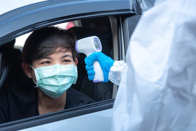 Medisch personeel met persoonlijke beschermingsmiddelen gebruikt een infrarood thermometerpistool om de lichaamstemperatuur te controleren op het drive-in-station in het ziekenhuis. nieuw normaal gezondheidszorg en medisch concept.
