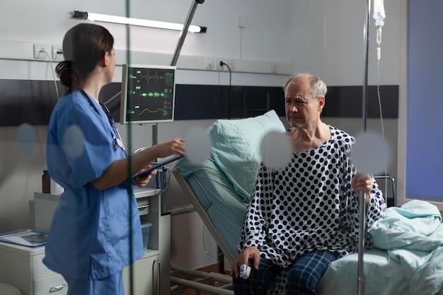 Medisch personeel met stethoscoop ondervragen zieke senior man zittend in bed met iv infuus, met pijnlijke uitdrukking