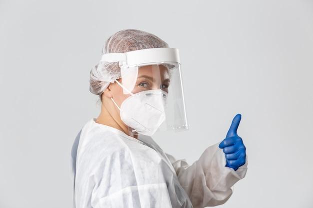 Medisch personeel, pandemie, coronavirus concept. brutale professionele vrouwelijke arts in persoonlijke beschermingsmiddelen, verzeker mensen allemaal onder controle, duimen omhoog en glimlachend