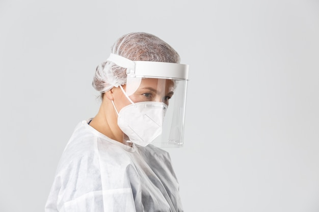 Medisch personeel, pandemie, coronavirus concept. profiel van ernstig ogende vrouwelijke arts in persoonlijke beschermingsmiddelen, gezichtsbescherming en gasmasker luisteren naar patiënt, controle verstrekken.