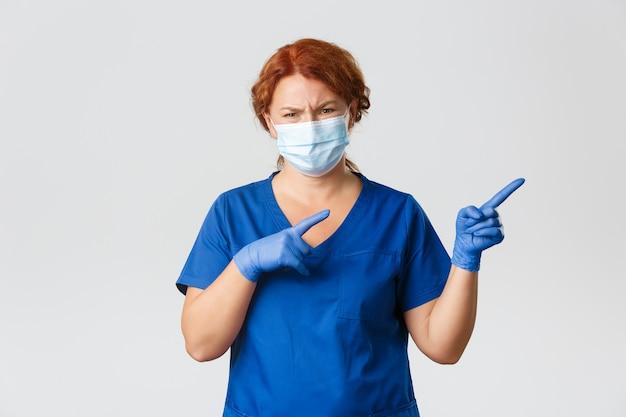 Medisch personeel, pandemie, coronavirus concept. sceptische en niet geamuseerde roodharige vrouwelijke arts, arts kijkt met oordeel, wijzende rechterbovenhoek met terughoudend gezicht, masker dragen
