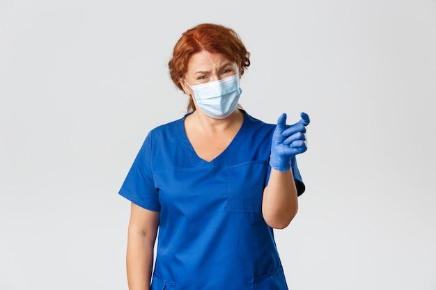 Medisch personeel, pandemie, coronavirus concept. teleurgestelde en klagende vrouwelijke arts, verpleegkundige of arts die iets te klein laat zien en er ontevreden uitziet, draag een gezichtsmasker en handschoenen.