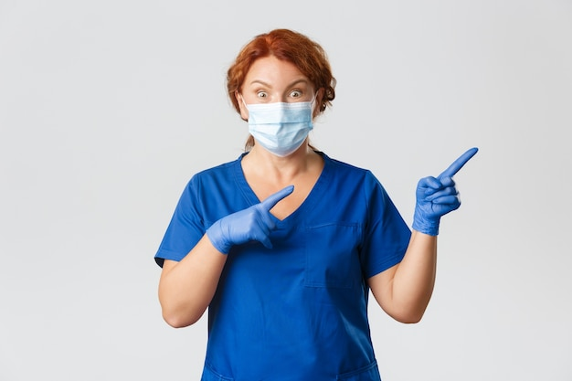 Medisch personeel, pandemie, coronavirus concept. verrast en onder de indruk vrouwelijke arts, arts van middelbare leeftijd met gezichtsmasker, handschoenen die rechtsboven met een verbaasde uitdrukking wijzen