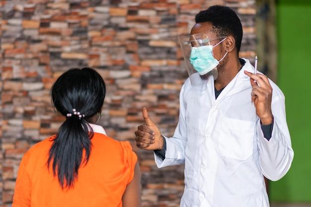 Medisch personeel steekt patiënt een duim omhoog na vaccinatie
