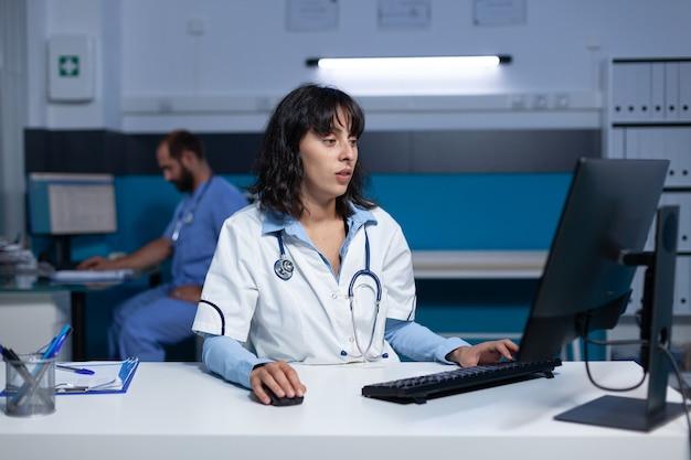Medisch specialist die 's nachts computer en toetsenbord gebruikt