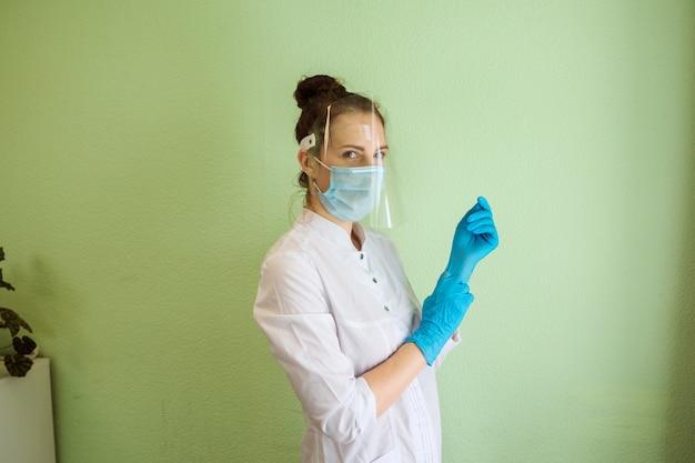 Medisch specialist, dokter draagt latex handschoenen, witte jurk, beschermend scherm en masker. binnen in de kliniek, voor groene muur.