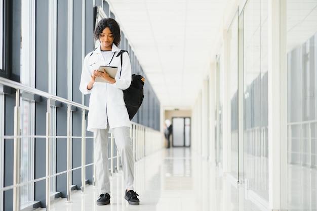 Medisch stageconcept. portret van jonge zwarte vrouwelijke arts student in witte jas.