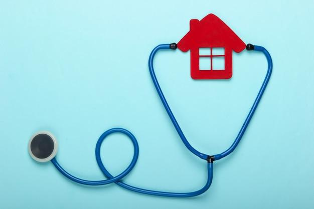Medisch stilleven. stethoscoop, beeldje van het ziekenhuis huis op blauwe achtergrond. plat leggen