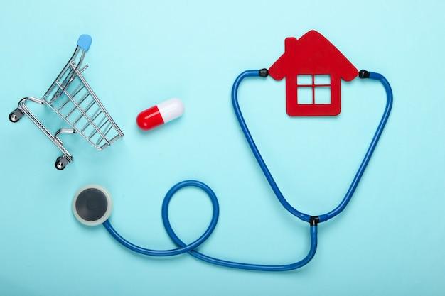 Medisch stilleven. stethoscoop, beeldje van het ziekenhuis huis, winkelwagentje met pil op blauwe achtergrond. plat leggen