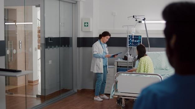 Medisch team controleert de vitale bewaking van de hartslag van de patiënt en helpt met een druppelzak voor vloeistoffen