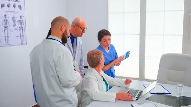Medisch team dat een discussie heeft over de diagnose van de patiënt die naar het laptopscherm in de vergaderruimte kijkt. kliniek deskundige therapeut bespreken diagnose over patiënten behandeling problemen record op de werkplek.