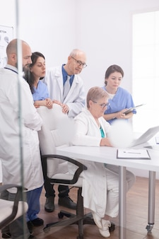 Medisch team dat een discussie heeft over de diagnose van de patiënt die naar het laptopscherm in de vergaderruimte kijkt. kliniek deskundige therapeut in gesprek met collega's over ziekte, medische professional.