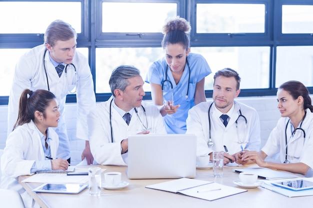 Medisch team dat laptop onderzoekt en een bespreking heeft bij conferentieruimte