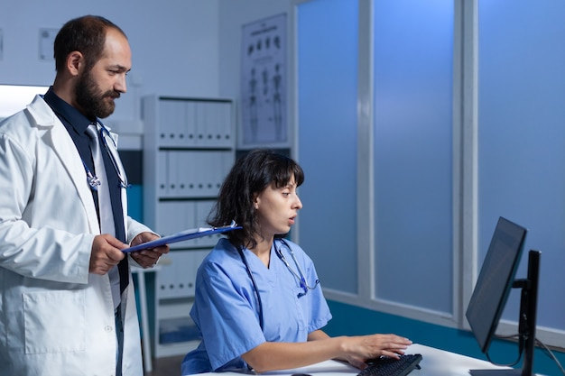 Medisch team van werknemers die naar de monitor voor de gezondheidszorg kijken