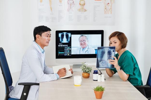 Medisch team videobellen met ervaren oncoloog om donkere vlek op thoraxfoto van patiënt te bespreken