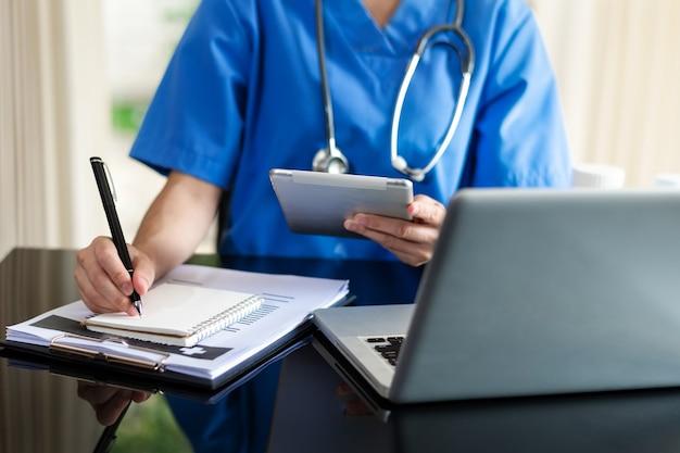 Medisch technologieconcept. dokter werkt met mobiele telefoon en stethoscoop en digitale tabletlaptop in modern kantoor in het ziekenhuis in ochtendlicht
