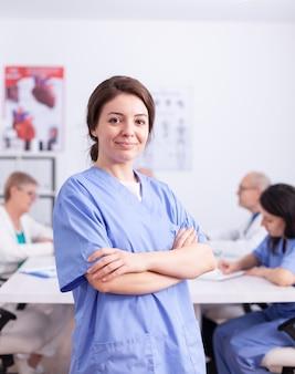 Medisch therapeut camera kijken met zorgpersoneel op de achtergrond uniform dragen. vriendelijke arts in de vergaderruimte van de kliniek, badjas, specialist.