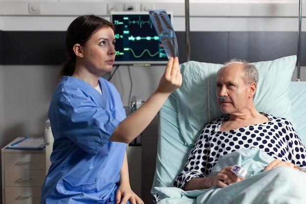 Medisch verpleegkundige analyseert senior patiënt xray in ziekenhuiskamer