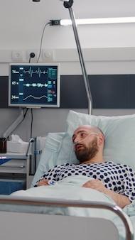 Medisch verpleegkundige bespreekt ziektebehandeling met gehospitaliseerde zieke man die in bed rust tijdens revalidatietherapie op ziekenhuisafdeling