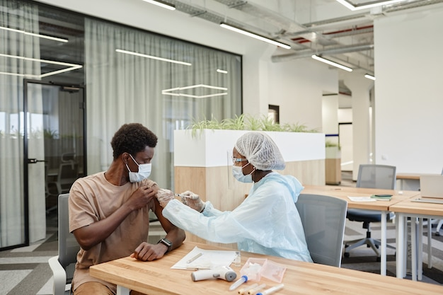 Medisch verpleegkundige in veiligheidshandschoenen en beschermend masker die vaccininjectie geeft tegen coronavirus aan p...