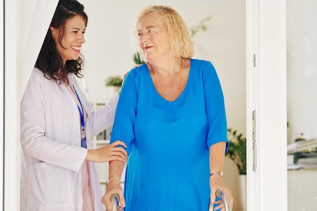 Medisch verpleegster die hogere patiënt helpt
