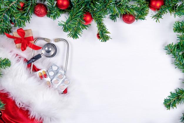 Medisch vlak met pillen, huidige giftdoos, stethoscoop en kerstboom op wit