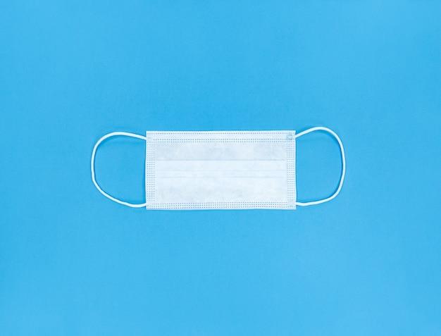 Medisch wegwerp gezichtsmasker op een blauwe achtergrond.