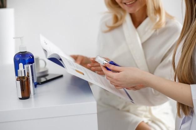 Medisch werker raadpleegt patiënt in witte hal van het ziekenhuis.