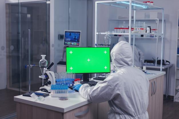 Medisch wetenschapper die op computer werkt met groen scherm op zijn werkplek. team van microbiologen die vaccinonderzoek doen en schrijven op apparaat met chroma key, geïsoleerd, mockup-display.