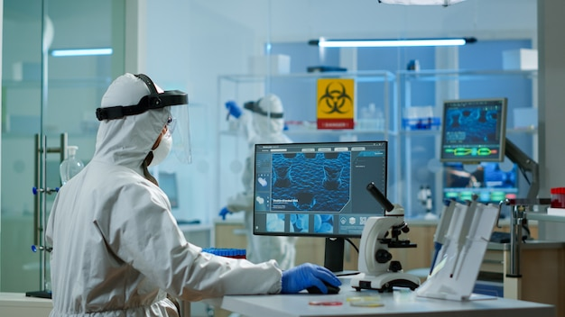 Medisch wetenschapper in ppe-pak die werkt met dna-scanbeeld typen op pc in uitgerust laboratorium. onderzoek naar de evolutie van vaccins met behulp van hightech- en scheikundige hulpmiddelen voor de ontwikkeling van wetenschappelijk onderzoek naar virussen