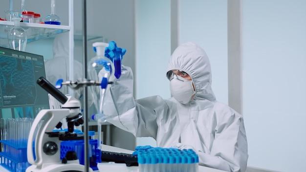 Medisch wetenschapper met overall in laboratoriumkamer voert tests uit met blauwe vloeistof bij het typen van reageerbuizen. artsen die de evolutie van het vaccin onderzoeken met behulp van hightech onderzoek naar de diagnose tegen het covid19-virus