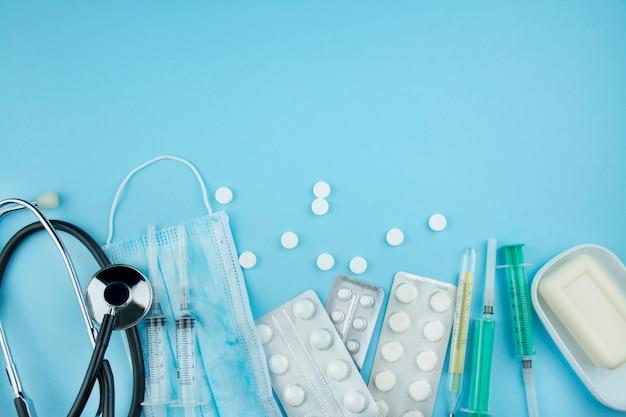 Medische achtergrond. medische uitrustingenstethoscoop, pillen, beschermend masker, thermometer op een blauwe achtergrond. het medicijn. kopieer ruimte. plat liggen.