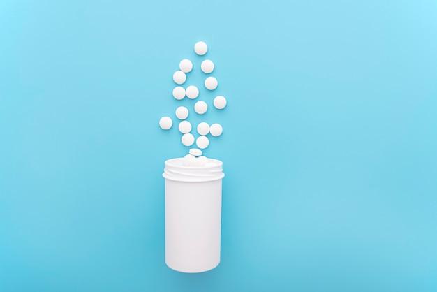 Medische achtergrond met witte fles en pillen op blauwe ondergrond, bovenaanzicht