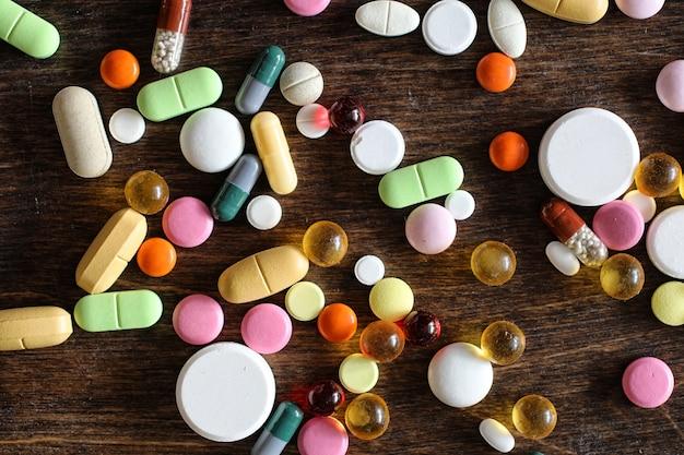 Medische achtergrond van verschillende kleurrijke medicijnen op een getextureerde houten