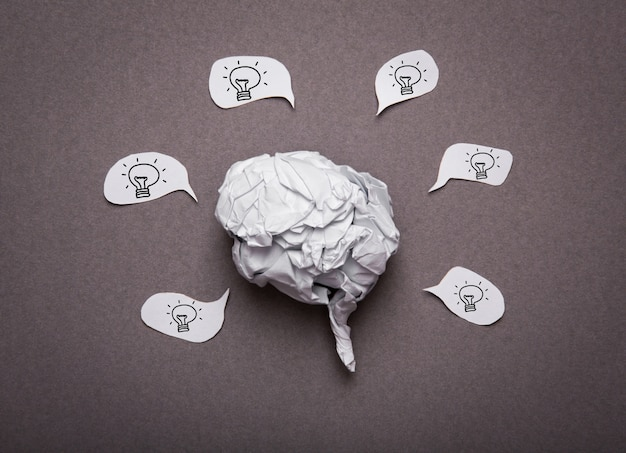 Medische achtergrond, verfrommeld papier brein vorm met gloeilamp