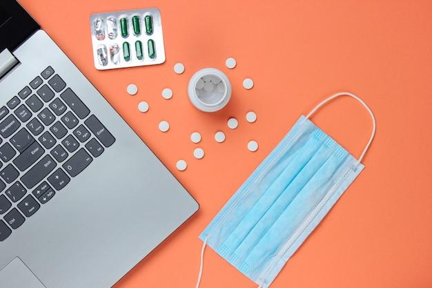 Medische achtergrond. werkruimte van een moderne arts. laptop, pillen, gaasmasker op perzik kleur achtergrond.