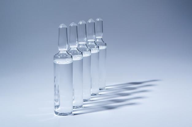 Medische ampullen voor injectie die op blauwe achtergrond wordt geïsoleerd
