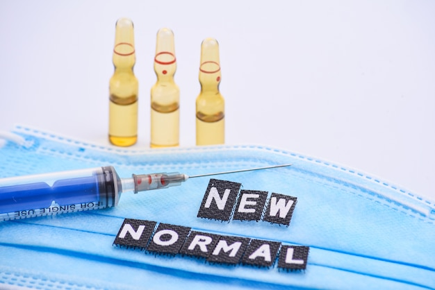 Medische ampullen voor injectie, spuit en medisch masker met inscriptie nieuw normaal. medicijnen en ziektebehandeling. farmacologie en wetenschap
