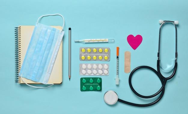 Medische apparatuur op een blauwe achtergrond. blarenpillen, blocnote, stethoscoop, spuit, thermometer. medisch concept, bovenaanzicht, plat lag stijl
