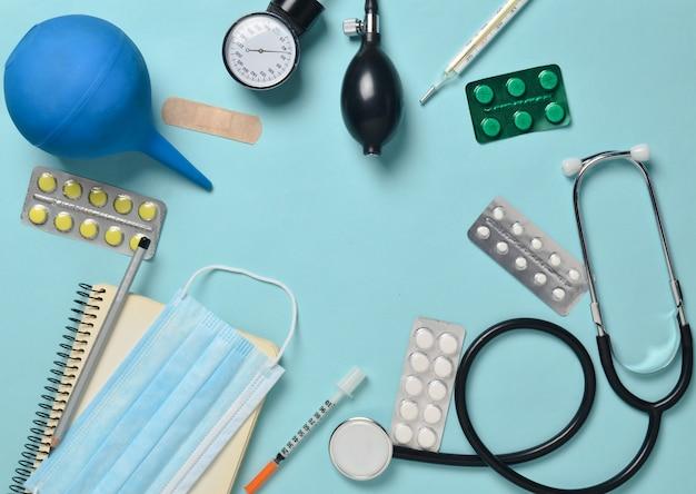 Medische apparatuur op een blauwe achtergrond. klysma, blisterpillen, blocnote, stethoscoop, spuit, thermometer, manometer. medisch concept, bovenaanzicht, plat lag stijl, kopie ruimte