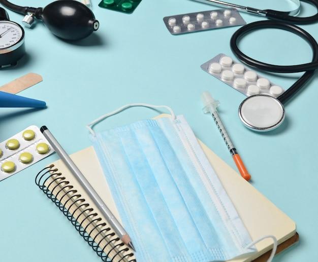 Medische apparatuur op een blauwe achtergrond. klysma, blisterpillen, blocnote, stethoscoop, spuit, thermometer, manometer. medisch concept, kopie ruimte