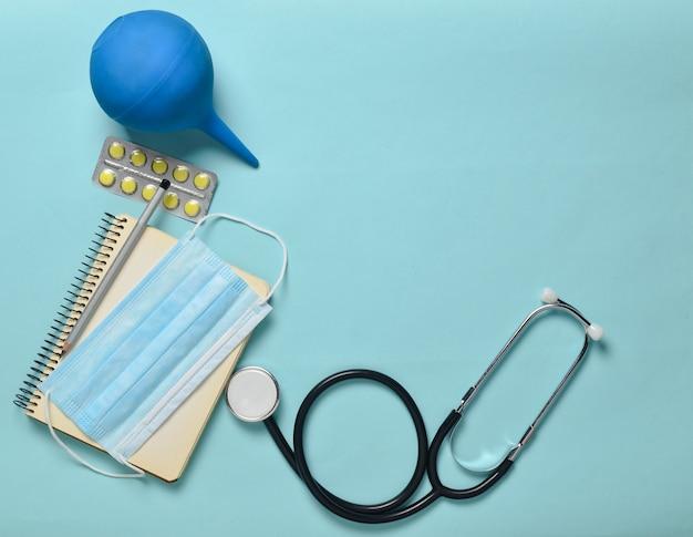 Medische apparatuur op een blauwe achtergrond. klysma, blisterpillen, blocnote, stethoscoop, spuit, thermometer. medisch concept, bovenaanzicht, plat lag stijl