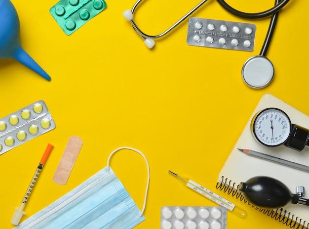 Medische apparatuur op een gele achtergrond. klysma, blisterpillen, blocnote, stethoscoop, spuit, thermometer, manometer. medisch concept, bovenaanzicht, plat lag stijl, kopie ruimte