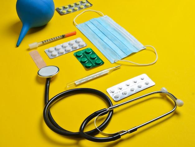 Medische apparatuur op een gele achtergrond. klysma, blisterpillen, blocnote, stethoscoop, spuit, thermometer. medisch concept